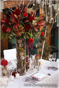 LOVE LOVE LOVE this Winter Wedding centerpiece!!! From The elegant drape of the red tulips to the pine cones on the vase!