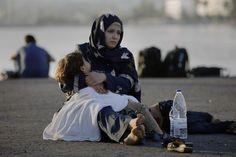 """Photographer Yannis Behrakis Location KOS, Greece Reuters / Saturday, August 15, 2015 A Syrian refugee holds her child in her arms as she sits in the port of the Greek island of Kos waiting to be registered and move with her family to the """"Eleftherios Venizelos"""" vessel August 15, 2015. REUTERS/Yannis Behrakis"""