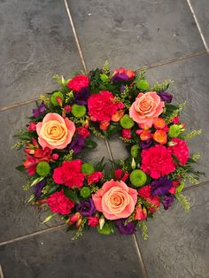 Vibrant wreath funeral flowers tribute design with roses and carnations in orange, cerise pink, purple and lime green Funeral Floral Arrangements, Pink Flower Arrangements, Christmas Flower Arrangements, Christmas Flowers, Flower Centerpieces, Flower Decorations, Flower Wreath Funeral, Funeral Flowers, Purple Wreath
