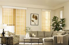 Graber Venetian blond Wood Blinds Northern Lights in a living room. Great combination of white valance, white cloth tape to highlight the tall windows.