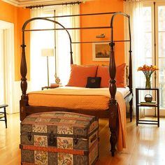 Light Bright A deep orange adds life to this bedroom. During the day the color is bold and energizing. At night its warm and cozy. The wooden bed frame, side table, and chair work together to ground the bright walls. The antique blanket chest at the foot of the bed brings together all the colors in the room.