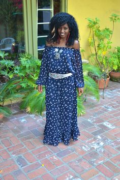 Off the shoulder dark navy floral dress cinched in with a white boho belt with turquoise detail. Loving the red drop eartings & feathers in her gorgeous afro.