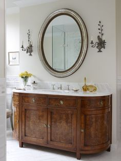 craftsman made this principal bathroom vanity based on a vintage furniture piece at Sarah's request. It features decorative baroque veneer panels and a Calacatta marble top.