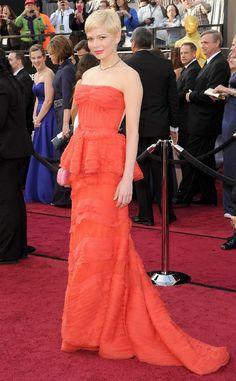 """Alfombra roja Oscar 2012: Michelle Williams de Louis Vuitton,con un vestido en color coral y silueta peplum. Williams competía por el Oscar como mejor actriz principal con la película """"My week with Marilyn""""."""