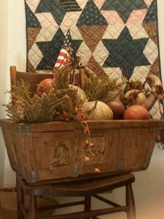 Prim Fall...quilt on the wall and old basket with pumpkins.