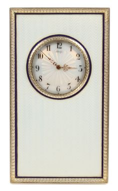 A FABERGE SILVER GILT AND ENAMEL DESK CLOCK, WORKMASTER HENRIK WIGSTROM, ST. PETERSBURG, CIRCA 1908-1917. Rectangular, in oyster white enamel over a wavy engine turned ground, the bezel and body outlined with a thin band of dark blue enamel. The sunburst enamel dial having black enamel Arabic numerals and pierced gold hands in the Louis XV style.