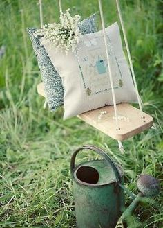 A touch of garden whimsy.  A little swing and cushion display.