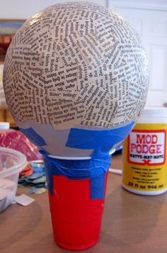 Paper Mache Bowls with Gelli™ Prints!  Creating your bowl is a simple process, but it does take patience! Here's what to do: Blow up a balloon and tie a knot. Place the balloon in a cup to stabilize it. It helps to secure the balloon to the cup with tape. Pour some Mod Podge into a dish and stir in a little water, thinning it to the consistency of heavy cream. A foam brush is good for applying the adhesive, but I prefer to wear disposable gloves and use my hands.