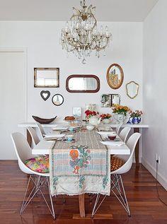 A mesa de jantar tem aparador acoplado, ambos com pés reaproveitados de um móvel rústico mineiro. Na parede, o efeito de vários espelhos agrupados. Os lustres de cristal e os bules com flores são relíquias de família da designer Ana Morelli