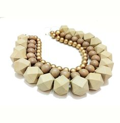 Three strands of faceted ivory painted wood beads, beige rounds and gold painted beads create this thick bib necklace. Sits high like a collar. Big, bold, regal, and lightweight for it's size. Irene Wood is a Seattle-based jewelry designer and painter inspired by color, history, textile.