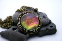 This color shifting pendant changes colors and sparkles as you turn it, from purple to pink, orange to yellow and green then to turquoise. The unique