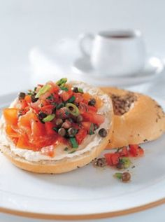 Bagels with smoked salmon - 4 plain or rye bagels 100 g (31⁄2 oz) neufchatel cream cheese 200 g (7 oz) sliced smoked salmon 2 spring onions (scallions), chopped 2 roma (plum) tomatoes, finely chopped 2 tablespoons baby capers, rinsed and drained 2 tablespoons finely chopped dill 2 tablespoons lemon juice 1 tablespoon extra virgin olive oil