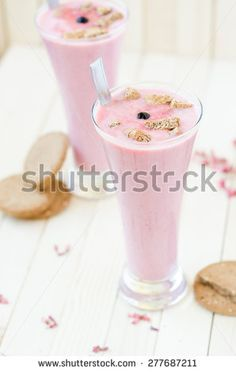 Pink Strawberry smoothie with brown cookies on light brown rustic table - stock photo