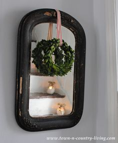 Vintage mirror with a boxwood wreath and peppermint stripe ribbon