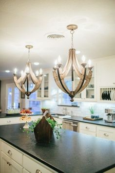 Neutral kitchen with honed black granite, a white Carrera marble tile backsplash, galvanized metal chandeliers. Rustic transitional. Magnolia Homes // Fixer Upper
