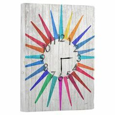 """Reclaimed wood wall clock with a multicolor starburst motif.   Product: Wall clockConstruction Material: Reclaimed woodColor: MultiFeatures: Ready to hangAccommodates: (1) Battery - includedDimensions: 20"""" H x 14"""" W"""