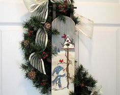 This Christmas wreath, has a burlap bow with three rusted jingle bells hanging down. Rusted sleigh sits bottom right. Seed pod sprays radiate out from bow. Beautiful cones are scattered about wreath. This is a very clean looking wreath, not over done, but a lovely simple statement. The wreath is about 24 around. Bells jingle when moved. This contains real pine cones