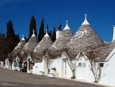 Trulli strung along via Monte Pertica in Alberobello, province of Bari, Italy. The whitewashed symbols were added following the restoration of the stone roofs in the 1980s and 1990s.