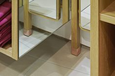 Oak wall-mounted ladders with copper accent Mirror-clad display boxes / Copper accessory hooks