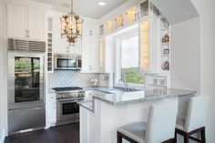 Chic kitchenette features a French lantern illuminating white cabinets paired with grey marble countertops.