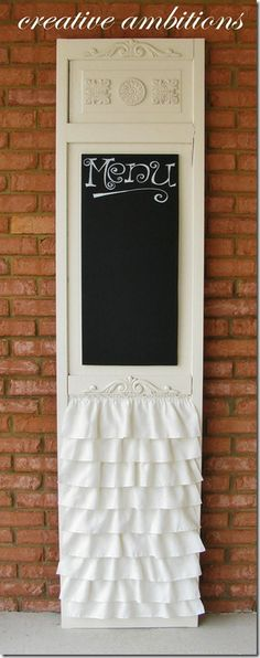 An old door, chalkboard paint, wood appliques, and a ruffle made from a tablecloth.