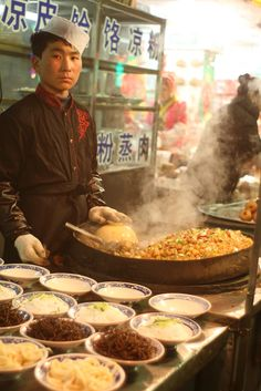 A large pan of rice in China, preparing noodles beside - such care goes into their traditional food