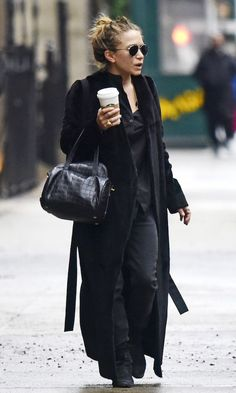 Mary-Kate Olsen was spotted in New York City in an all-black casual cool look with aviators, a belted maxi coat, button-down shirt, The Row bag, slouchy jeans, and boots.
