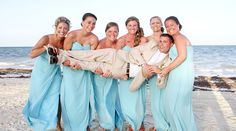 Bridesmaids hold groom for beach portrait. Pretty long bridesmaid dresses in Tiffany light blue! | Palace Resorts #destinationwedding