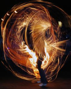 new years celebration, fire poi, golden orange light trails.