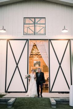 Couple photographed in front of beautiful white barn doors | Image by Jacie Marguerite Photography