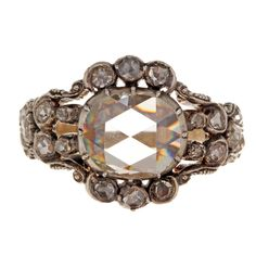 Early Dutch Rose Cut Diamond Ring. Dutch Hallmarks date this ring from 1853 to 1865. One large rose cut diamond surrounded by many small rose cuts set in silver on gold. A rare example that includes diamonds all the way around the band.