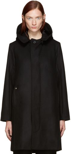 Long sleeve felted wool coat in black. Button tab fastening at hood. Concealed button closure at front. Seam pockets at waist. Box pleat with button fastening at back hem. Pockets at fully lined interior. Tonal stitching.