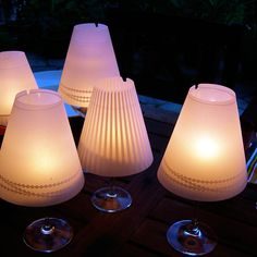 Mini lamp shades on wine glasses with candles in them
