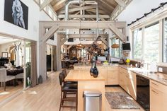 Covered Bridge House - Wooden beams frame the corridor-style layout, with exposed ductwork and a lofty ceiling above