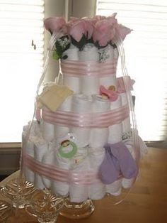 Diaper Cake for a Baby Girl. Used Pampers swaddlers diapers and lots of rubber bands, then hot glued the ribbon around the diapers on the edge of ribbon. So fun to do!