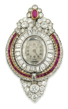 AN ART DECO RUBY AND DIAMOND LAPEL WATCH. Of lozenge form, the central oval watch with polished Arabic numerals and hands beneath a faceted portrait diamond dial, to a baguette-cut diamond bezel, within a further calibré ruby and single-cut diamond bombé border, with similarly-set foliate surmount and diamond shield shaped terminal, the outer border circa 1930, French marks for platinum, later adapted. Watch dial signed Unimex, ruby and diamond frame numbered. #ArtDeco #LapelWatch