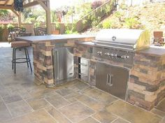 """my newly landscaped backyard, including a Coyote 36"" grill and refrigerator."""