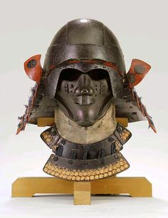 Zunari Kabuto and Ryubu-men (Mask for High-ranking Military Officials). Muromachi period (16th c), with signature Katsumasa saku and Hikotohara [Myochin Katsumasa (active 1532-1554)], simple russet-iron bowl with an exaggerated front plate extending at the sides over the temples and cheeks and down to a peak at the forehead, the brow fitted with an amakusa mabisashi (wavy peak) and small fukigaeshi (turnbacks) decorated with family crests of gingko leaves finished in shakudo.