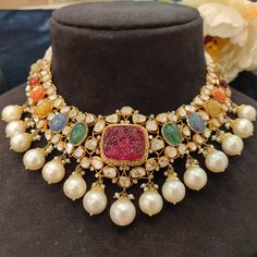 An unusual uncut diamond necklace, detailed with natural navratan and a carved red Ruby in the centre, flanked by south-sea pearls. . . An…