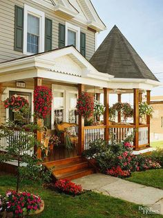A makeover added Victorian style and more space for outdoor living and entertaining. The peaked roof entryway and gazebo with turret roof both feature hanging baskets overflowing with shade-loving flowers. This remodeled porch is ready for spring and summer nights.