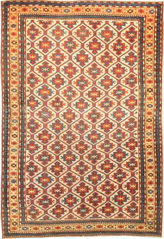 A Kazak rug - A late 19th century Kazak rug with a beige field beneath a bold polychrome geometric trellis with restrained floral motifs in red, ...