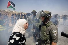 A Palestinian woman argues with an Israeli border policeman during a protest against Jewish settlements in the West Bank village of Nabi Saleh, near Ramallah, Sept. 4, 2015.