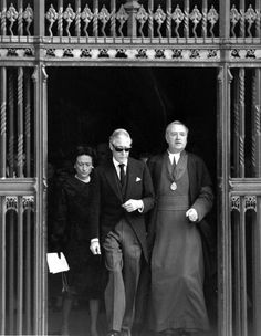The Duchess of Windsor (1896 - 1986), the Duke of Windsor (1894 - 1972), who reigned as King Edward VIII in 1936, and the Dean of Westminster leave Westminster Abbey by the Dean's Yard exit after attending the memorial service for the Duke's sister Mary, Countess of Harewood (1897 - 1965).