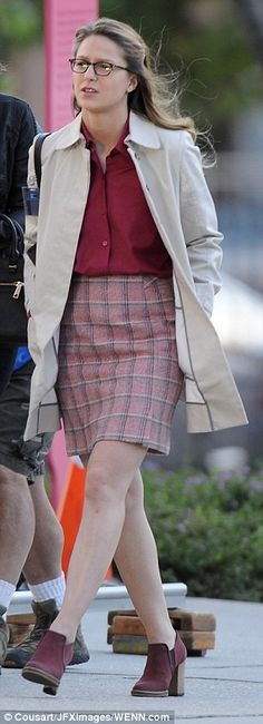 Kara Danvers AKA Supergirl in a maroon shirt and matching checked skirt with a beige raincoat and some chunky maroon heels