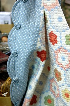 I love the hexies, the fact that the border and binding are the same fabric, and the scalloped edging with yo yos.