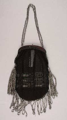 Date Made: 1900-1920  Description:  Purse; black crochet with silver steel beaded looped fringe. Bottom is closely crocheted, middle has an elongated open net design, top half in a net motif. Silvertone frame with double chain handle. Steel bead tassels on either side of frame. Looped fringe at bottom.