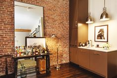 Brick walls, wood floors, brown cabinets, white marble countertop, silver floor lamp, minibar, and large mirror