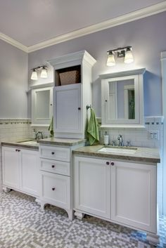 Mosaic tile floors add punch to this traditional bathroom, which has an overall clean, updated aesthetic. The dual vanity is footed, giving it the appearance of a piece of built-in furniture. Meanwhile, a pair of medicine cabinets and a tall center cabinet feature molding that ties in with the crown molding, and also with decorative tile molding that caps a subway tile wainscot.