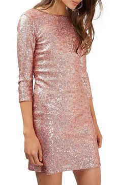 A sizzling body-con dress splashed with light-catching pink sequins is styled with a scooped back and three-quarter-length sleeves.