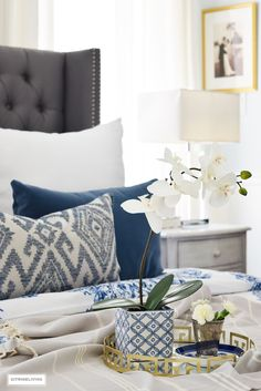 Gorgeous blue and white bedroom featuring blue and white bedding paired with global inspired textiles, grey upholstered bed and brass accents and lighting bring a bright and airy look to any bedroom. Layer your bed with small luxuries to create a true ret